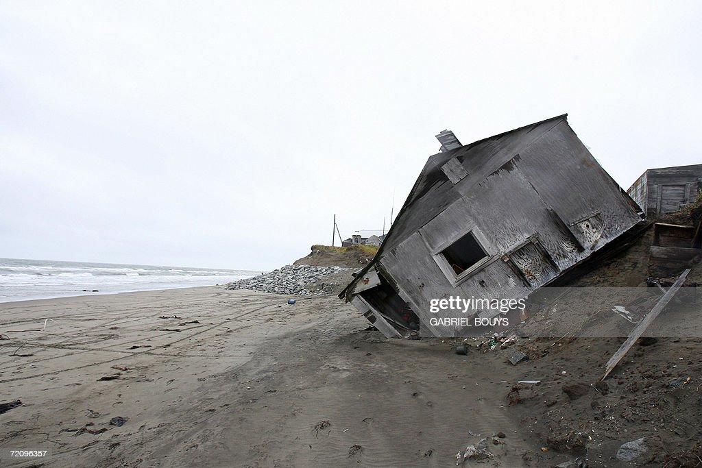 A home destroyed by beach erosion lies on its side 27 September 2006 in the the Alaskan village of Shishmaref. The village, home of Inupiat Eskimos, is located some 600 miles (965kms) northwest of Anchorage but just 110 miles (177kms) from the east coast of Russia. Shishmaref, on an island reachable only by air and inhabited for 4,000 years, is facing evacuation because of global warming. Temperatures that have risen 15F (4.4C) over the last 30 years are causing a reduction in sea ice, thawing of permafrost along the coast, making the shoreline vulnerable to erosion. The census of 2000 reported there were 562 people, 142 households, and 110 families residing in the village all facing evacuation and the loss of their traditional life. AFP PHOTO/GABRIEL BOUYS