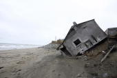 A home destroyed by beach erosion lies on its side 27 September 2006 in the the Alaskan village of Shishmaref The village home of Inupiat Eskimos is...