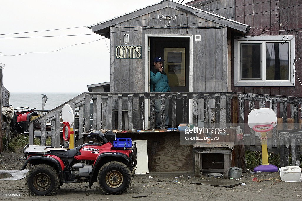 A man smoke a cigarette in front of his house in Shishmaref, Alaska, 27 September 2006. The village, home of Inupiat Eskimos, is located 20 miles (32kms) south of the Artic Circle. Shishmaref, on an island reachable only by air and inhabited for 4,000 years, is facing evacuation because of global warming. Temperatures that have risen 15F (4.4C) over the last 30 years are causing a reduction in sea ice, thawing of permafrost on which the village was built and making the shoreline vulnerable to erosion. Scientist report that other Alaskan towns are suffering similar problems, but point to Shismaref as an indicator of what can be expected in other parts of the world. Residents are planning to relocate to the mainland, making them the first refugees of global warming. AFP PHOTO/GABRIEL BOUYS