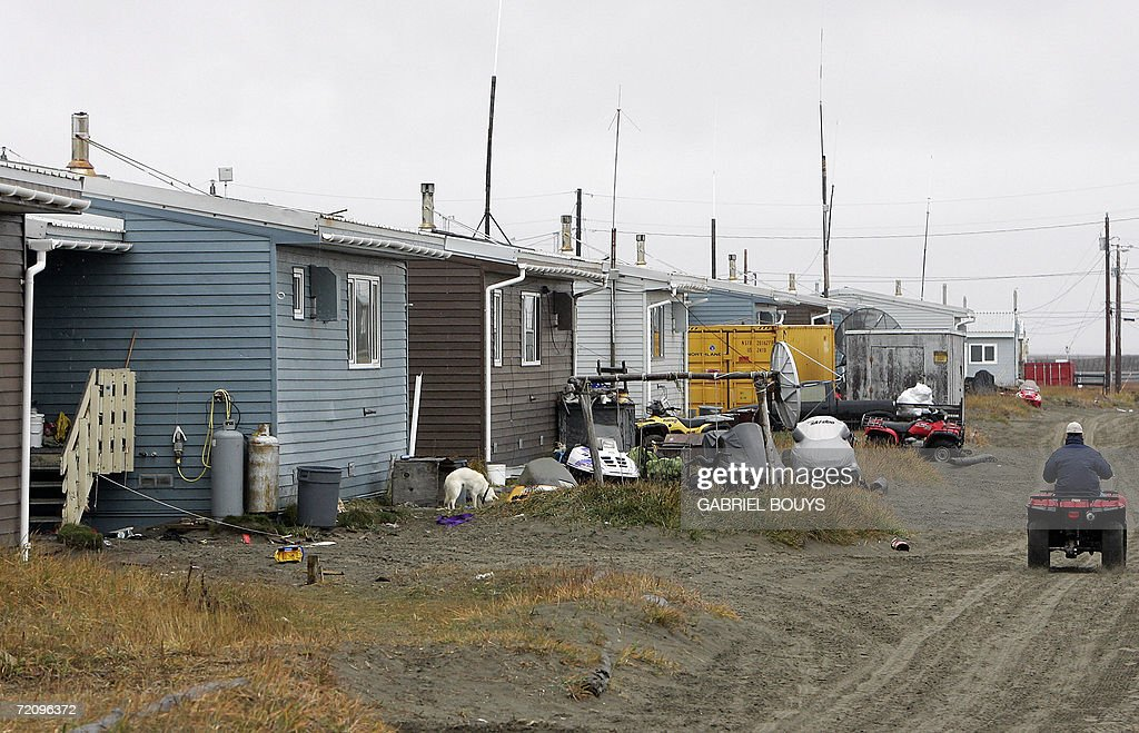 A resident rides past homes in Shishmaref, Alaska, 27 September 2006. The village, home of Inupiat Eskimos, is located 20 miles (32kms) south of the Artic Circle. Shishmaref, on an island reachable only by air and inhabited for 4,000 years, is facing evacuation because of global warming. Temperatures that have risen 15F (4.4C) over the last 30 years are causing a reduction in sea ice, thawing of permafrost on which the village was built and making the shoreline vulnerable to erosion. Scientist report that other Alaskan towns are suffering similar problems, but point to Shismaref as an indicator of what can be expected in other parts of the world. Residents are planning to relocate to the mainland, making them the first refugees of global warming. AFP PHOTO/GABRIEL BOUYS