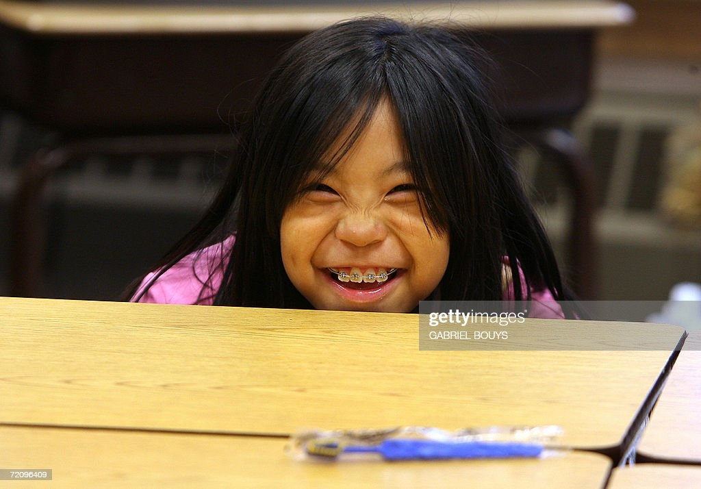 A students smiles from behind her desk at the school in Shishmaref, Alaska, 27 September 2006. The village, home of Inupiat Eskimos, is located 20 miles (32kms) south of the Artic Circle. Shishmaref, on an island reachable only by air and inhabited for 4,000 years, is facing evacuation because of global warming. Temperatures that have risen 15F (4.4C) over the last 30 years are causing a reduction in sea ice, thawing of permafrost on which the village was built and making the shoreline vulnerable to erosion. Scientist report that other Alaskan towns are suffering similar problems, but point to Shismaref as an indicator of what can be expected in other parts of the world. Residents are planning to relocate to the mainland, making them the first refugees of global warming. AFP PHOTO/GABRIEL BOUYS