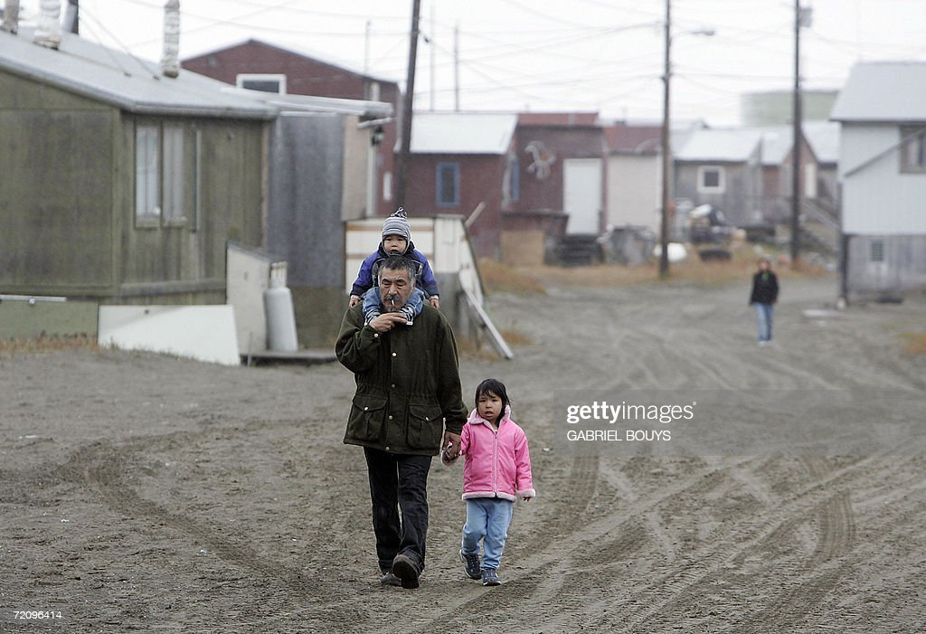 An resident takes his children to school in Shishmaref, Alaska, 27 September 2006. The village, home of Inupiat Eskimos, is located 20 miles (32kms) south of the Artic Circle. Shishmaref, on an island reachable only by air and inhabited for 4,000 years, is facing evacuation because of global warming. Temperatures that have risen 15F (4.4C) over the last 30 years are causing a reduction in sea ice, thawing of permafrost on which the village was built and making the shoreline vulnerable to erosion. Scientist report that other Alaskan towns are suffering similar problems, but point to Shismaref as an indicator of what can be expected in other parts of the world. Residents are planning to relocate to the mainland, making them the first refugees of global warming. AFP PHOTO/GABRIEL BOUYS