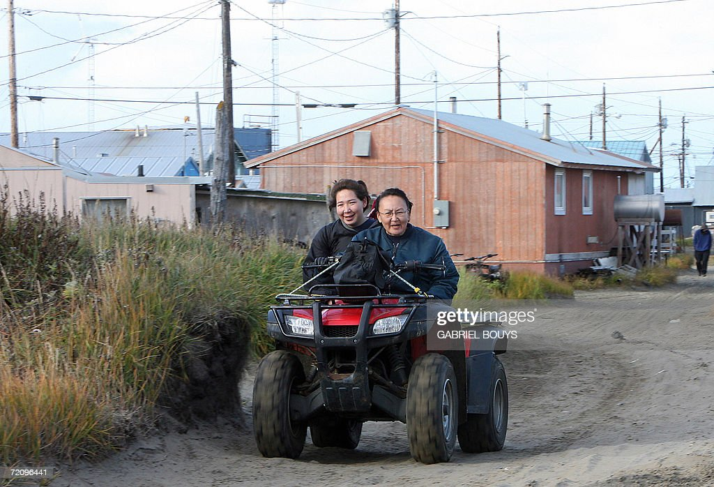 Mother and daughter ride an all-terrain vehicle in Shishmaref, Alaska, 26 September 2006. The village, home of Inupiat Eskimos, is located 20 miles (32kms) south of the Artic Circle. Shishmaref, on an island reachable only by air and inhabited for 4,000 years, is facing evacuation because of global warming. Temperatures that have risen 15F (4.4C) over the last 30 years are causing a reduction in sea ice, thawing of permafrost on which the village was built and making the shoreline vulnerable to erosion. Scientist report that other Alaskan towns are suffering similar problems, but point to Shismaref as an indicator of what can be expected in other parts of the world. Residents are planning to relocate to the mainland, making them the first refugees of global warming. AFP PHOTO/GABRIEL BOUYS