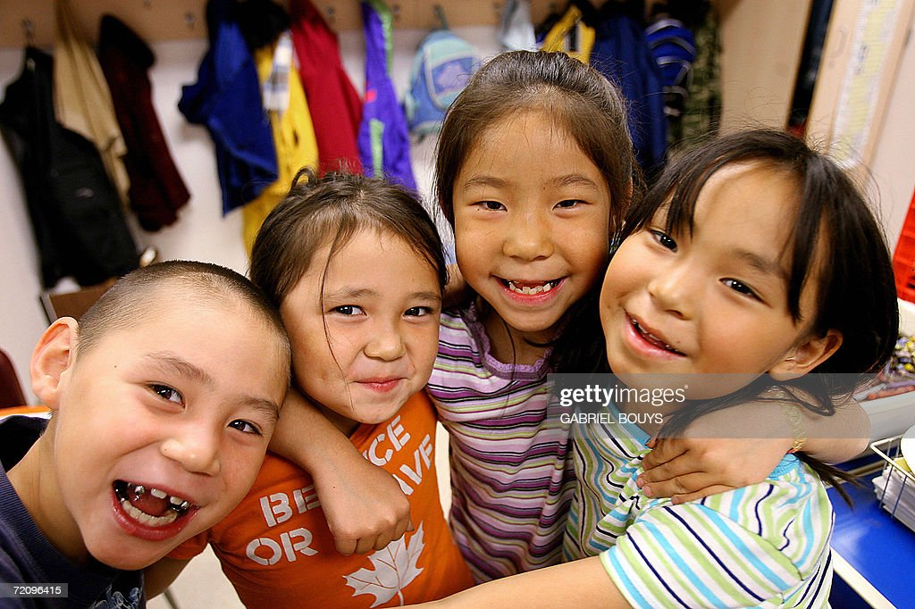 Students smile during a break at the school in Shishmaref, Alaska, 27 September 2006. The village, home of Inupiat Eskimos, is located 20 miles (32kms) south of the Artic Circle. Shishmaref, on an island reachable only by air and inhabited for 4,000 years, is facing evacuation because of global warming. Temperatures that have risen 15F (4.4C) over the last 30 years are causing a reduction in sea ice, thawing of permafrost on which the village was built and making the shoreline vulnerable to erosion. Scientist report that other Alaskan towns are suffering similar problems, but point to Shismaref as an indicator of what can be expected in other parts of the world. Residents are planning to relocate to the mainland, making them the first refugees of global warming. AFP PHOTO/GABRIEL BOUYS