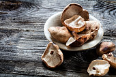 vegetable still life - Shitake mushrooms in stone cup set on genuine old wood background, studio shot