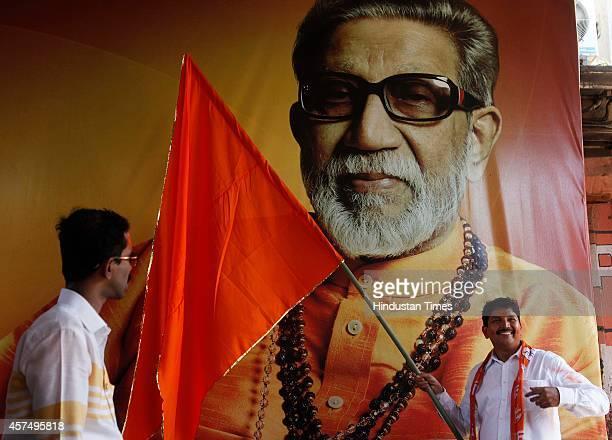 Shiv Sena leader Arvind Bhosale poses alongside the portrait of late Shiv Sena patriarch Baba Saheb Thackeray after the results of Maharashtra...