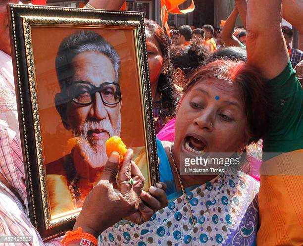 Shiv Sena supporters celebrate with the portrait of late Shiv Sena patriarch Baba Saheb Thackeray after the results of Maharashtra assembly elections...