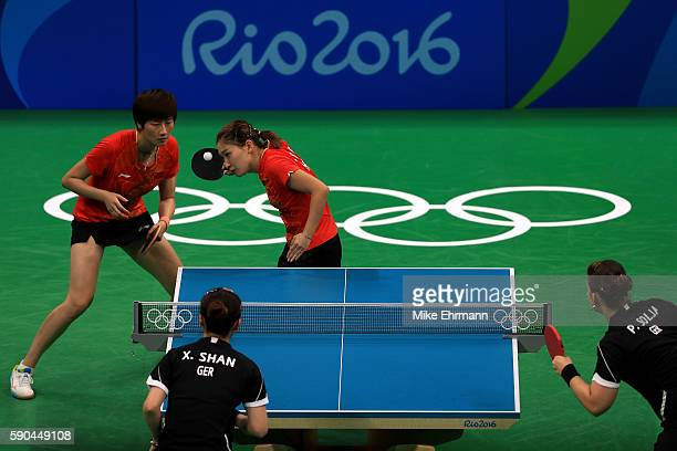 Shiwen Liu and Ning Ding of China play a doubles match against Petrissa Solja and Xiaona Shan of Germany in the Women's Team Gold Medal Team Match...
