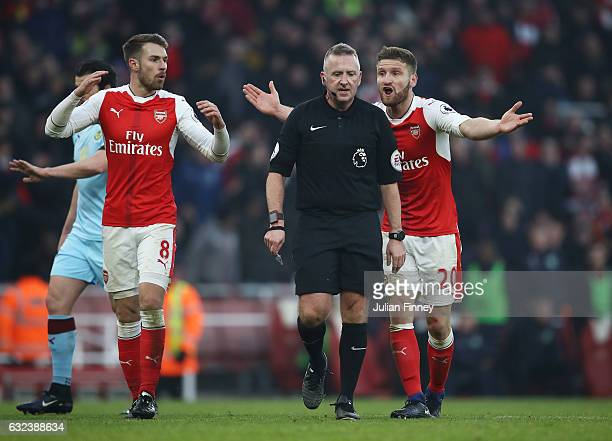Shkodran Mustafi and Aaron Ramsey of Arsenal protest to referee Jonathan Moss over the penalty decision during the Premier League match between...