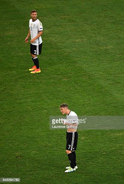 Shkodran Mustafi and Bastian Schweinsteiger of Germany react after France's second goal during the UEFA EURO semi final match between Germany and...