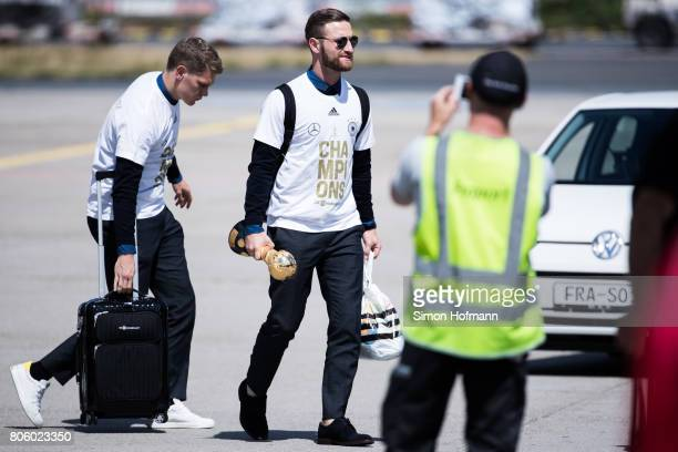 Shkodran Mustafi carries the World Cup Trophy as he departs the plane carrying the Germany National Football Team during the arrival at Frankfurt...