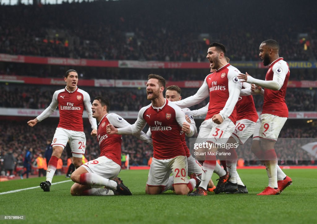 Shkodran Mustafi celebrates scoring the 1st Arsenal goal with (L) Granit Xhaka (2ndR) Sead Kolasinac and (R) Alex Lacazette during the Premier League match between Arsenal and Tottenham Hotspur at Emirates Stadium on November 18, 2017 in London, England.