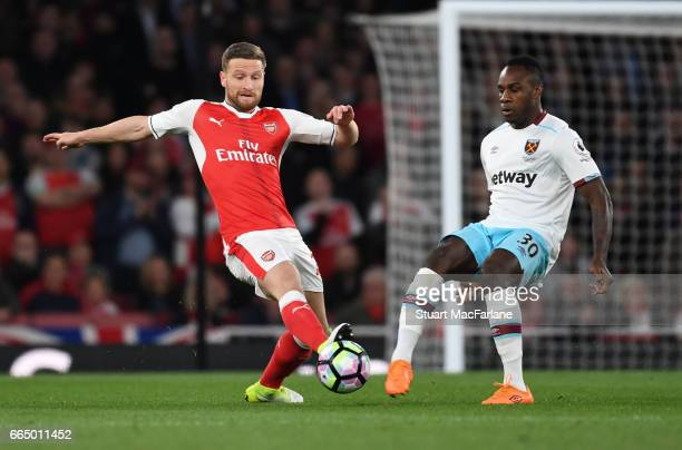 Shkodran Mustafi of Arsenal challenges Michael Antonio of West Ham during the Premier League match between Arsenal and West Ham United at Emirates...