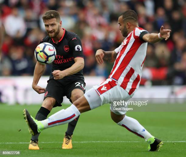 Shkodran Mustafi of Arsenal passes the ball past Jese during the Premier League match between Stoke City and Arsenal at Bet365 Stadium on August 19...
