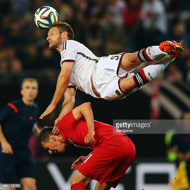 Shkodran Mustafi of Germany outjumps Arkadiusz Milik of Poland during the international friendly match between Germany and Poland at Imtech Arena on...
