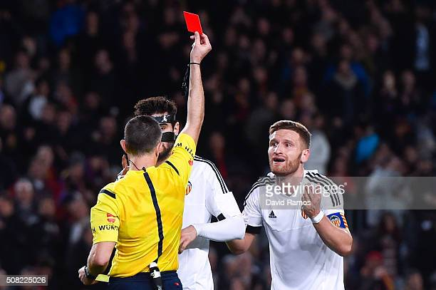 Shkodran Mustafi of Valencia CF is shown a red card by the referee Ignacio Iglesias Villanueva for a challenge on Lionel Messi of FC Barcelona during...