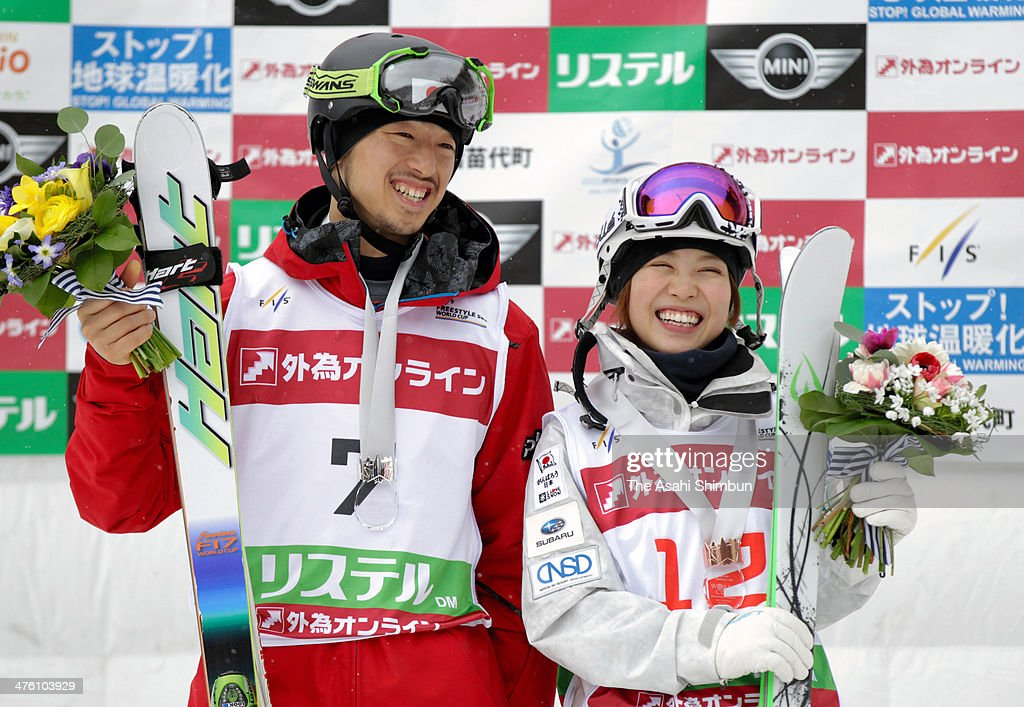 Sho Endo and Junko Hoshino of Japan pose for photographs with local kids during 2014 FIS Free Style Ski World Cup Inawashiro at Listel Inawashiro on...