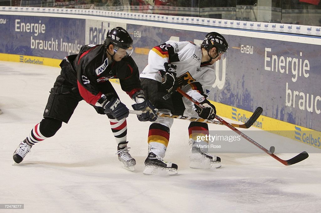 Sho Sato of Japan and Michael Bakos of Germany fight for the puck during the EnBW German Nations Cup match between Germany and Japan at the TUI Arena...