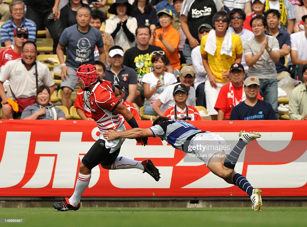 Sho Takenaka (L) of Japan XV runs with the ball to score a try during the match between Japan XV and French Barbarians at Prince Chichibu Stadium on June 24, 2012 in Tokyo, Japan.
