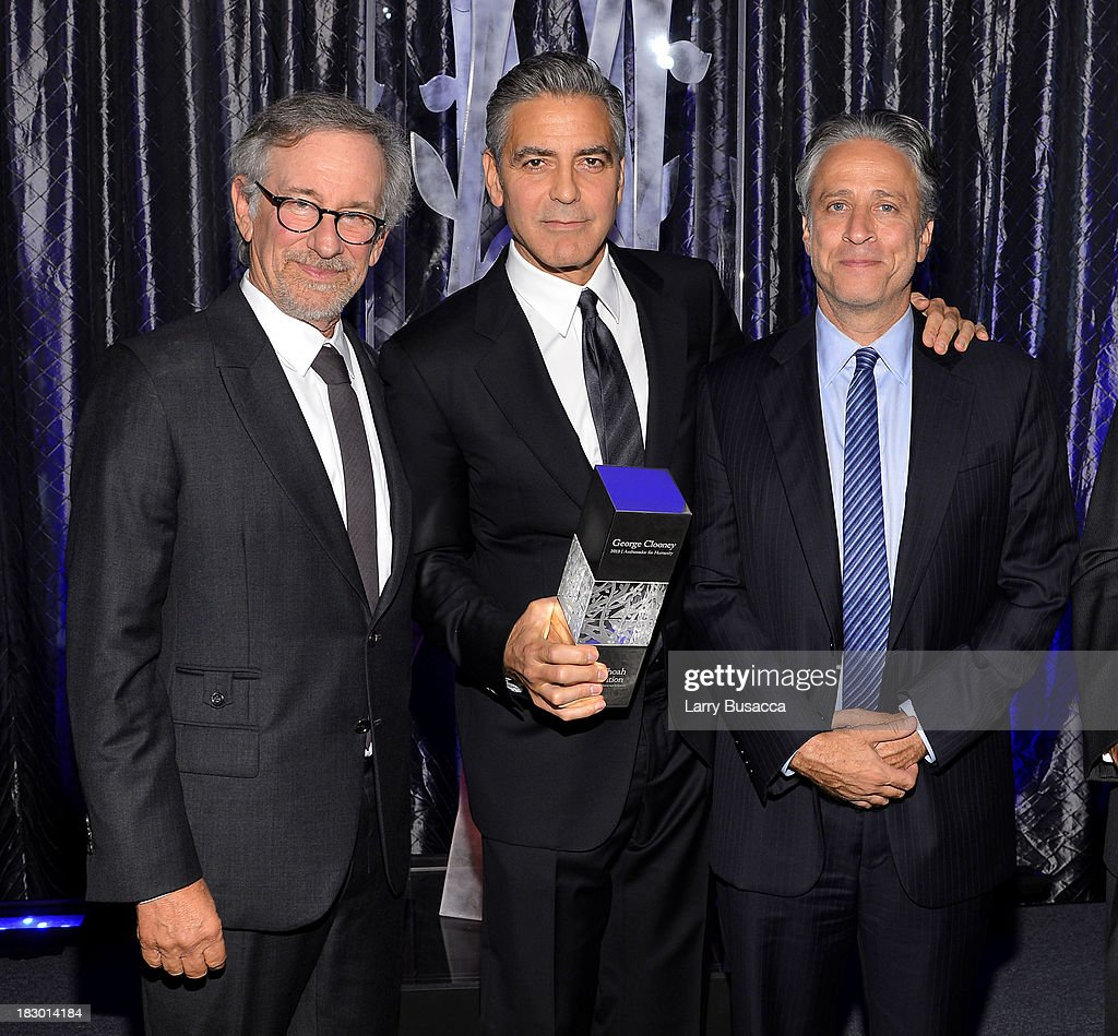 USC Shoah Foundation's Ambassador for Humanity Award winner <a gi-track='captionPersonalityLinkClicked' href=/galleries/search?phrase=George+Clooney&family=editorial&specificpeople=202529 ng-click='$event.stopPropagation()'>George Clooney</a> (C) poses with <a gi-track='captionPersonalityLinkClicked' href=/galleries/search?phrase=Steven+Spielberg&family=editorial&specificpeople=202022 ng-click='$event.stopPropagation()'>Steven Spielberg</a> (L) and <a gi-track='captionPersonalityLinkClicked' href=/galleries/search?phrase=Jon+Stewart+-+Political+Satirist&family=editorial&specificpeople=202151 ng-click='$event.stopPropagation()'>Jon Stewart</a> at the USC Shoah Foundation Institute 2013 Ambassadors for Humanity gala at the American Museum of Natural History on October 3, 2013 in New York, New York.