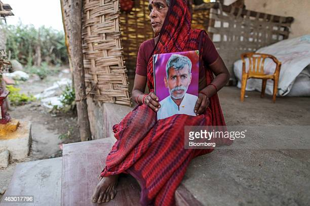 Shobha Singh Bais sits for photograph while holding an image of her deceased husband Govind outside her house in Yavatmal Maharashtra India on...