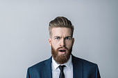 Shocked bearded businessman with open mouth looking at camera