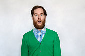 Shocked man with thick ginger beard, isolated on gray