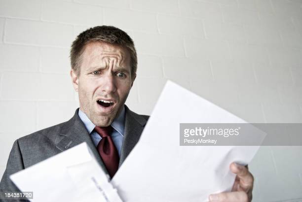 Shocked Businessman Looks Disappointed Opening a Letter