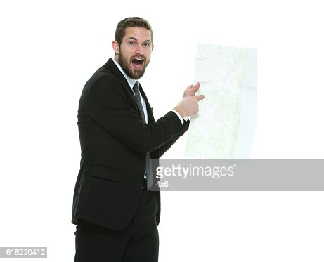 Shocked businessman pointing at map : Stock Photo
