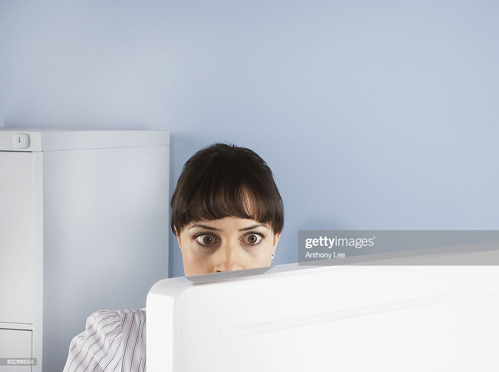 Shocked businesswoman looking at computer : Stock Photo