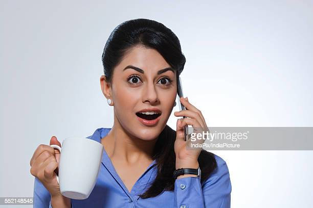 Shocked businesswoman with coffee mug answering call against gray background