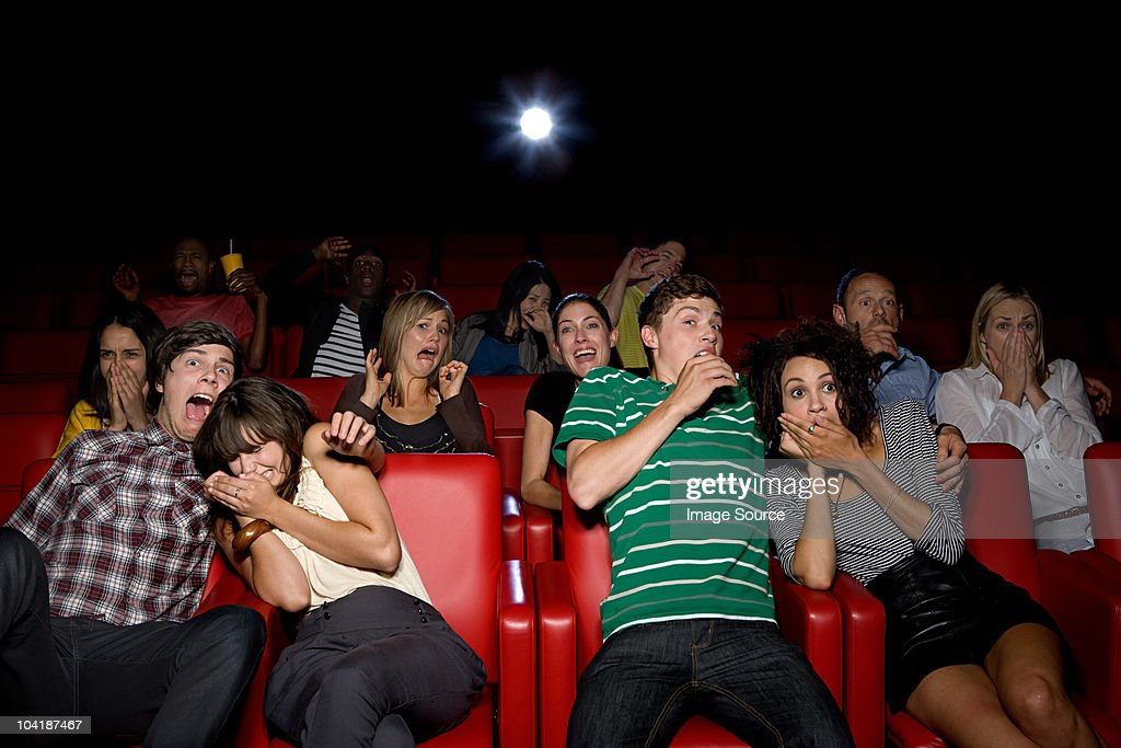 Shocked couples in the movie theater : Stock Photo