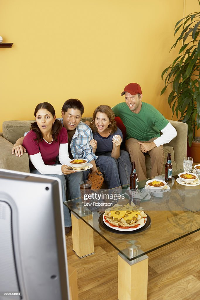 Shocked friends watching television together : Stock Photo