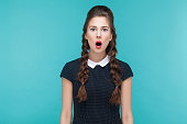 Shocked girl looking at camera with stress and open mouth. Indoor, studio shot on blue background