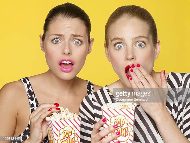 shocked girls eating popcorn watching a film