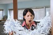 Shocked Hispanic businesswoman holding  shredded papers