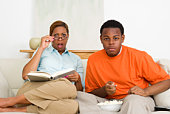 Shocked mother with book watching TV with son