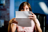 A woman looking at her mail (letter or bills)  in disbelief, shock!