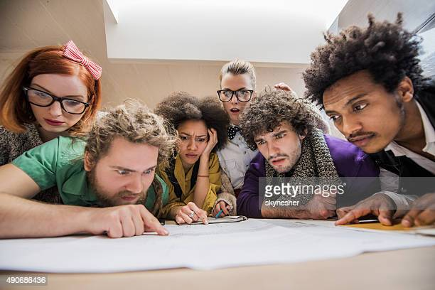 Shocked start-up team working on blueprints in office.