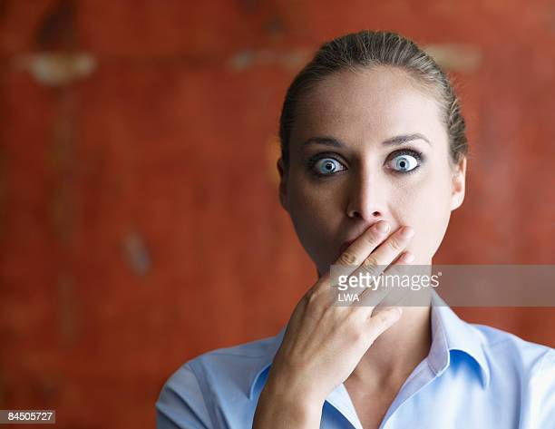 Shocked Woman Covering Mouth with Hand