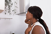 Close-up Of A Shocked African Woman Looking At Mold On Wall