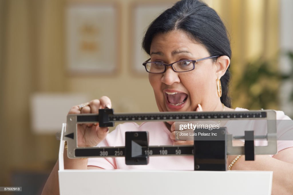Shocked woman weighing herself : Stock Photo