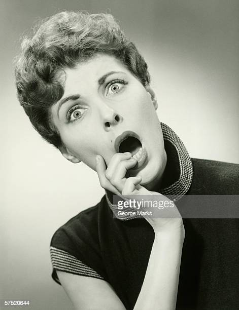 Shocked woman with fingers on lips in studio, (B&W), portrait