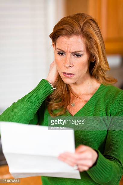 Shocked woman with open mouth reading credit card statement