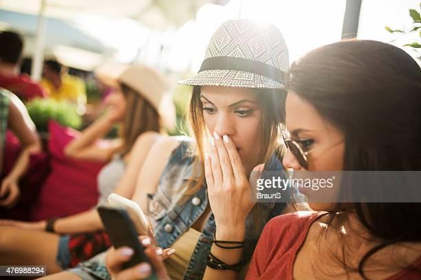 Espantado mulher a ler uma mensagem de texto de telemóvel.