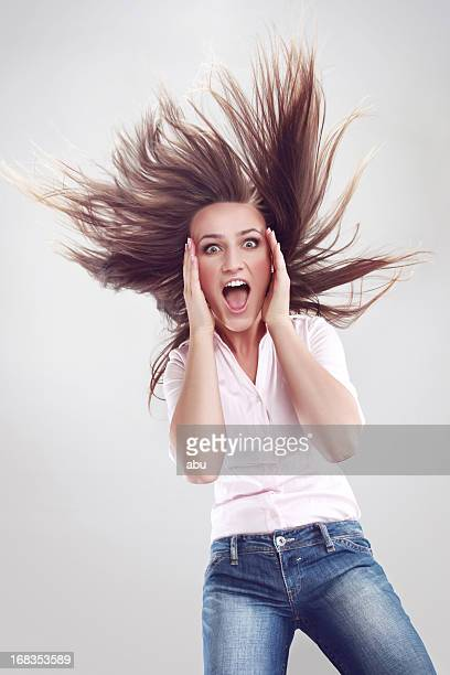 Shocked young woman with hair up in the air