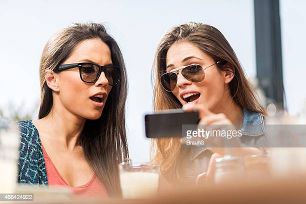 Shocked young women using mobile phone in a cafe.