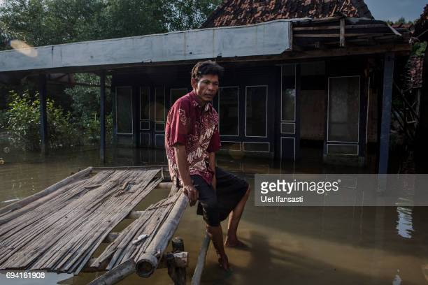Shodik sits in front of his abandoned family house which surrounded by rising sea levels at Bedono village on June 7 2017 in Demak Indonesia...