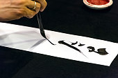 Detail on the hand of a japanese shodo calligraphist writing something with a brush and black ink
