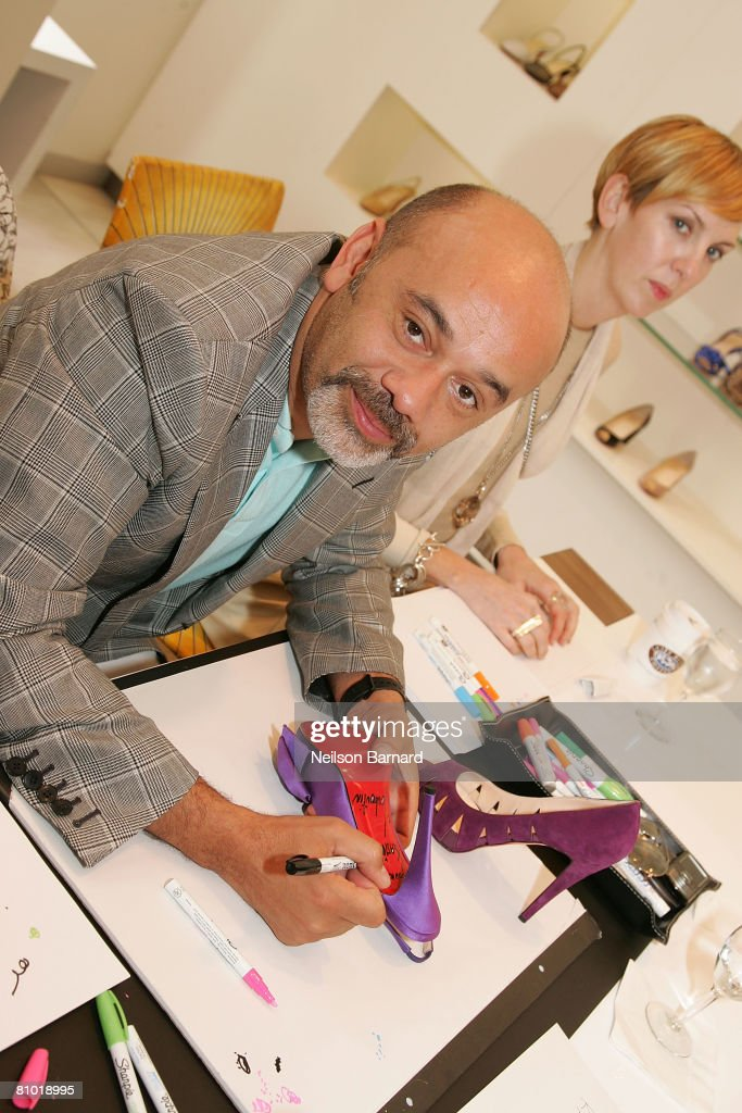 Shoe designer Christian Louboutin signs customers shoes at the launch of his new fall collection at Barneys New York on May 7, 2008 in Beverly Hills, California. (Photo by Neilson Barnard/Getty Images)Christian Louboutin